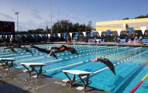 Carlmont and Woodside swimmers dive off the blocks to begin the heat.