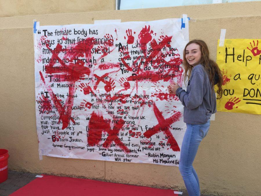 Maddie Standlee, a sophomore, stands in front of a poster covered in derogatory comments made by public figures. The quotes are being painted over for an activity celebrating Gender Equality Week.