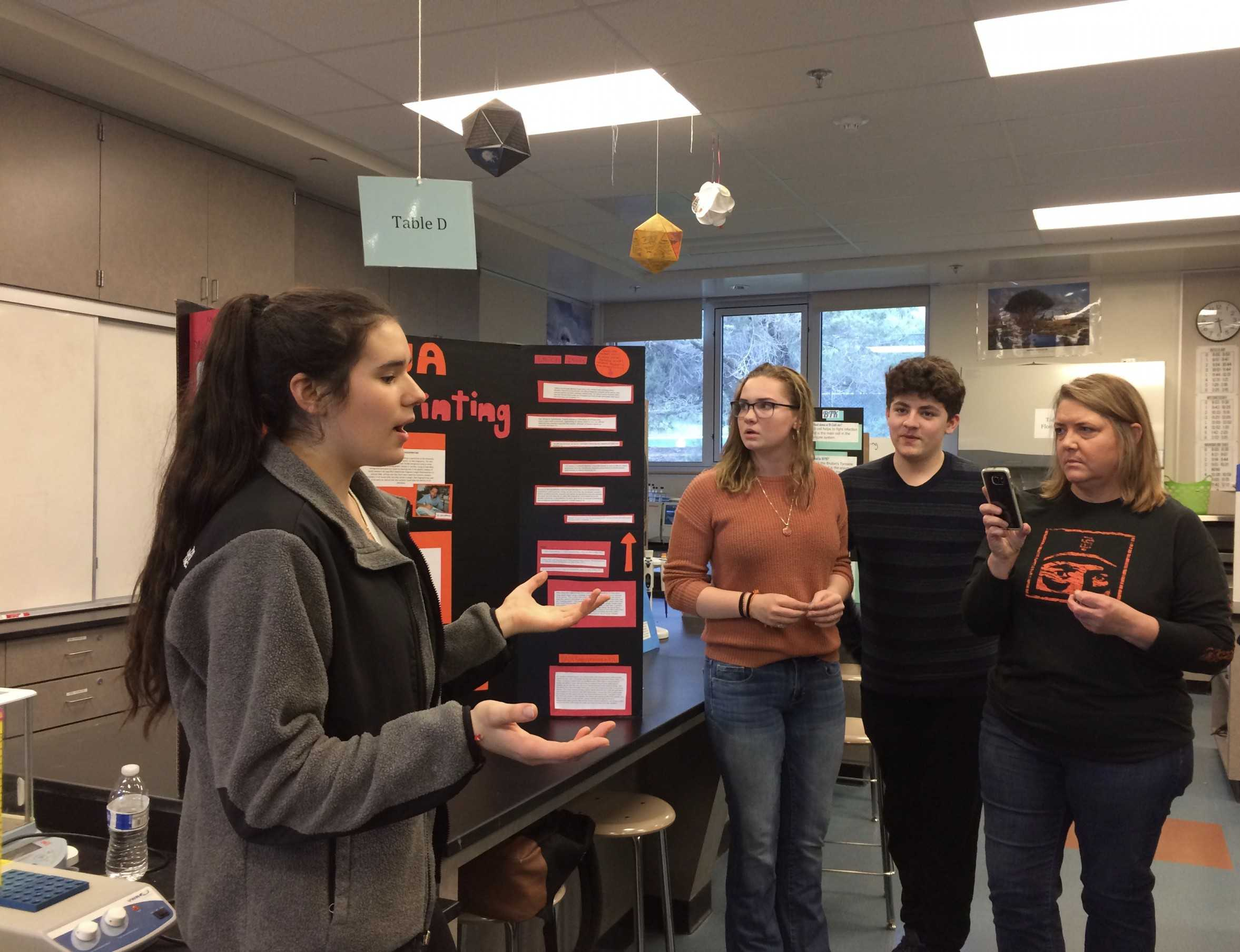 Sophomores Tiara Testa, Jessie Zorb, and Terby Diesh present their biotechnology project on DNA fingerprinting to a group of parents.