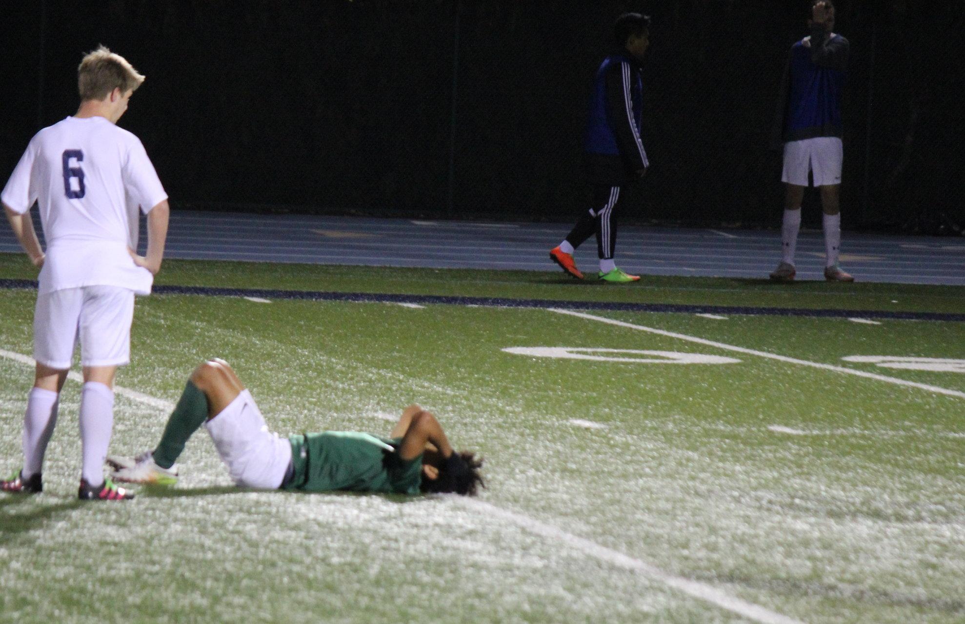 Junior midfielder Ben Zaino looks over downed Monterey player.