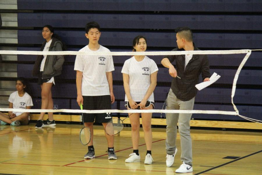 Coach Nathan Liang talks to players during their match