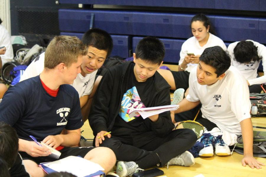Badminton junior varsity players spend their time off the court to study and do homework together.