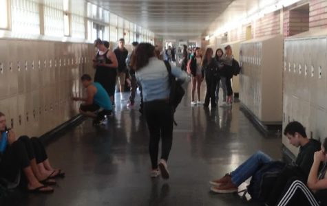 Students carry large backpacks improperly in the hallway, putting their backs at risk of injury.