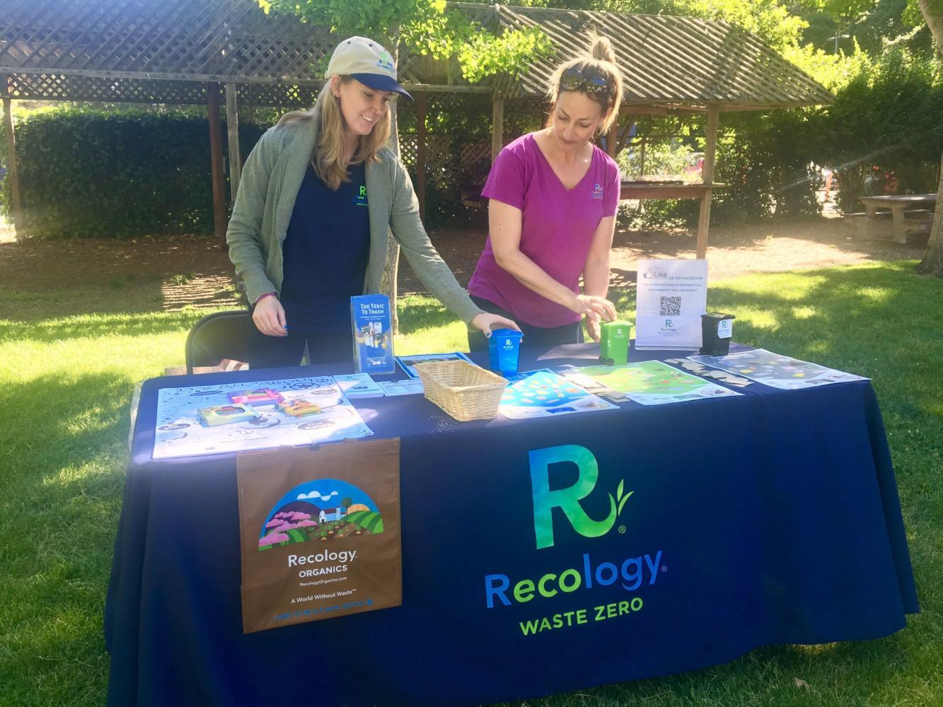 Gina Tretten and Rachael Lacey from Recology wait for people to stop by their booth.