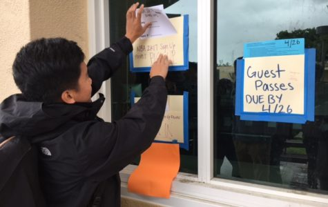 Liam Jocson, ASB president, drops blank sign-up sheets in a folder outside the ASB room.