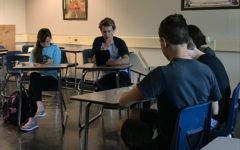 Philosophy Club members pay attention to their President Henry McCulloh who is reading the article of the day.