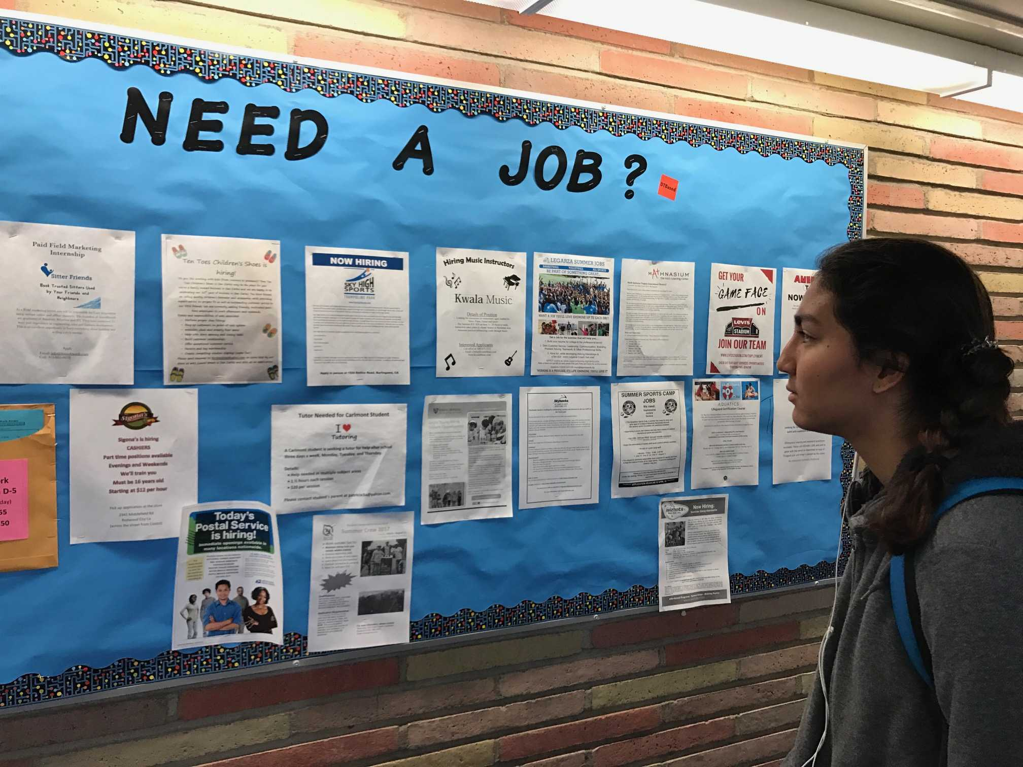 Sophomore Seema Wadhwa looks at the B-hall bulletin board before class. Wadhwa hopes to find an interesting job opportunity.