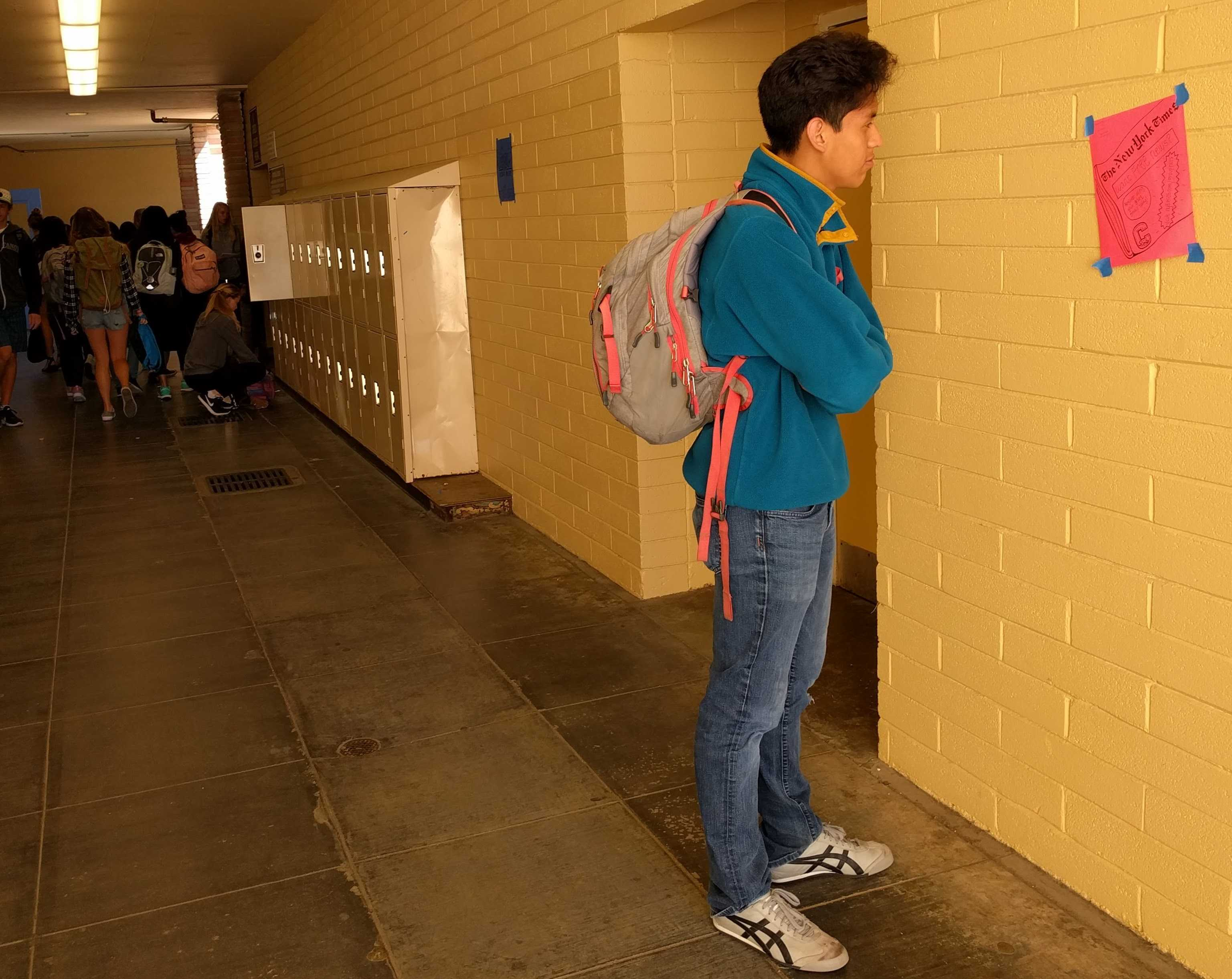 Sophomore William Castro-Ramirez examines a poster for an upcoming school activity.