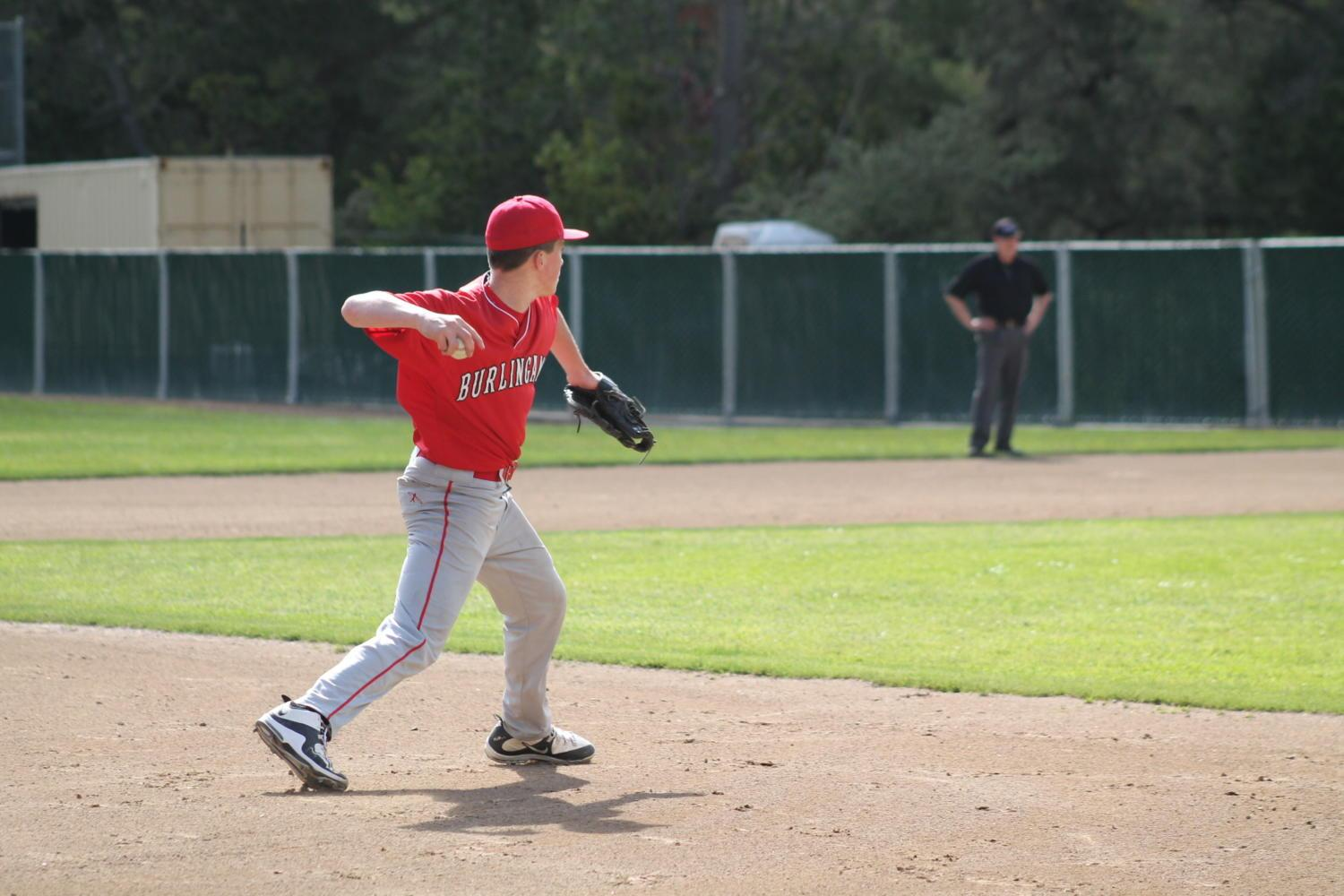 Burlingame sophomore Chase Funkhouser warms up before the game by throwing a ball to first base.
