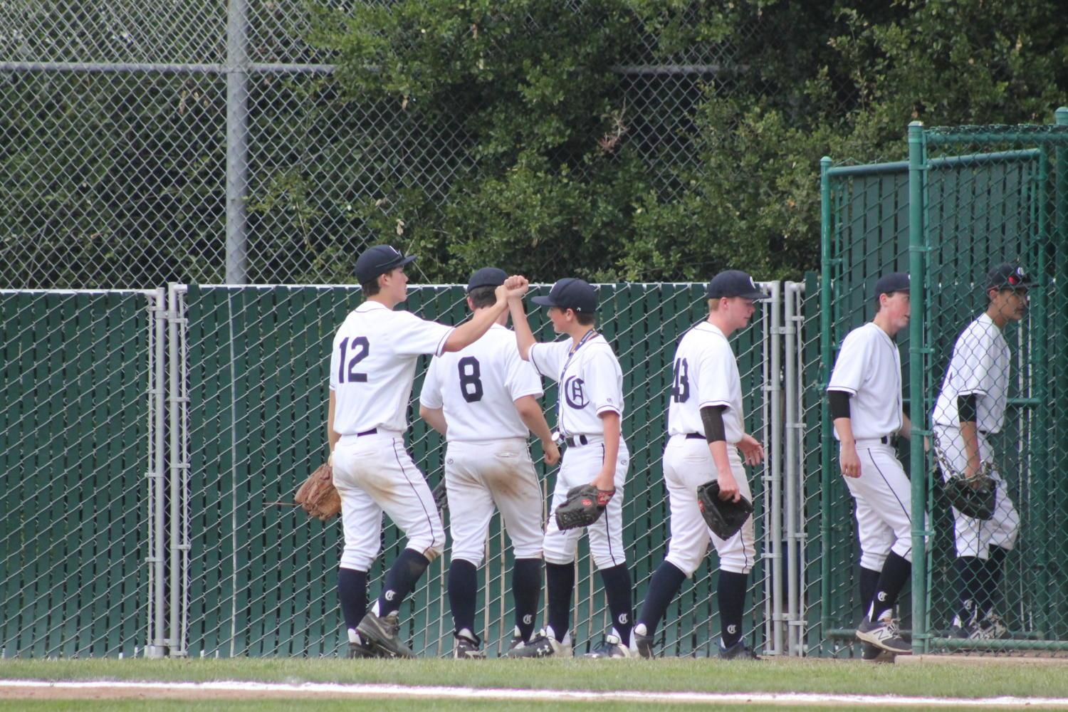 Carlmont teammates congratulate each other on the way to the next inning.