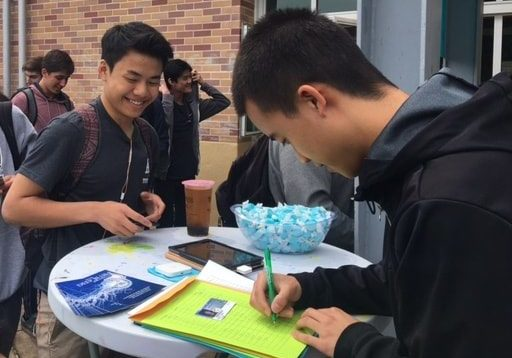 Justin Wang, a junior and the finance commission supervisor, helps fellow junior Alec Tung buy his prom ticket.