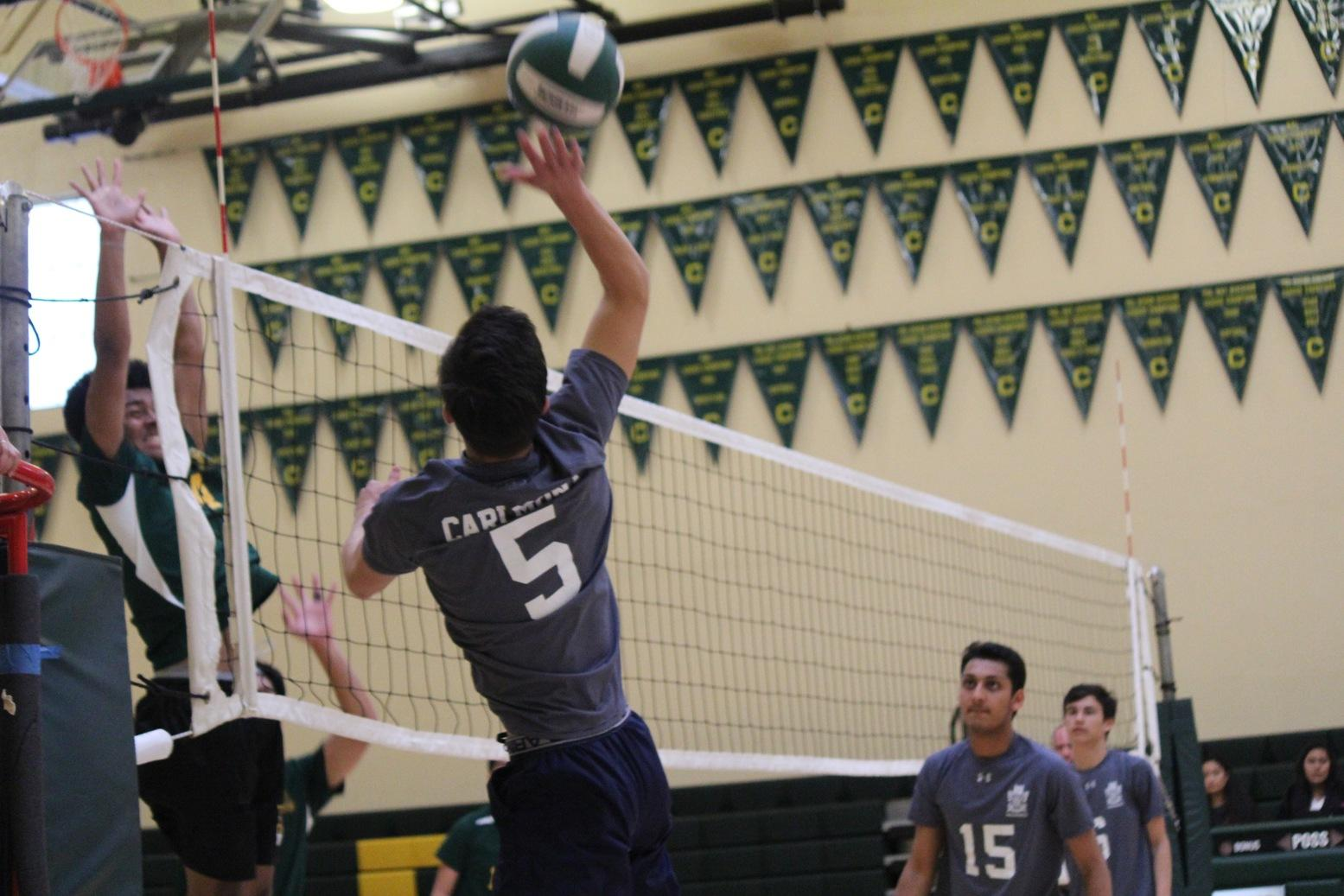 Jason Jung, a senior hits the ball over the net earning a point for the Scots