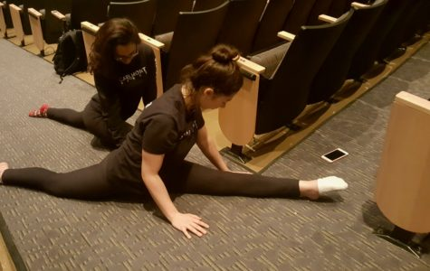 Before going on stage to practice for the spring show, Georgia Van Amsterdam, a junior in intermediate dance, and Moriah Meskin, a senior in intermediate dance, are stretching in the aisles of the theater in the performing arts building.