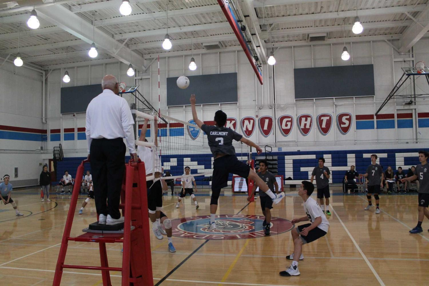 Christopher Ding, a senior, tips the ball over the net to get past Hillsdale blockers.
