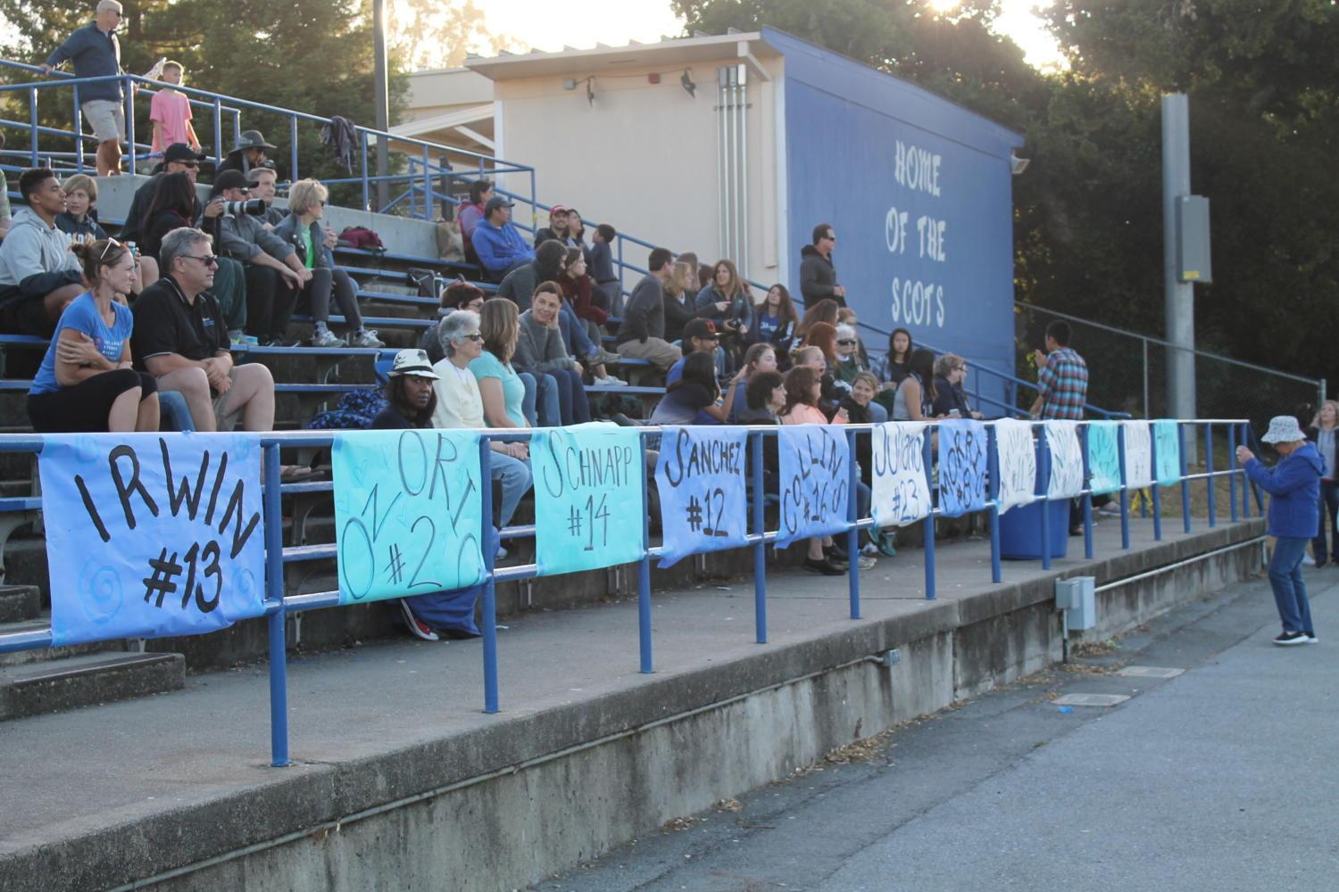 Posters for all 12 Carlmont seniors line the stands of the stadium during the game against Sequoia.