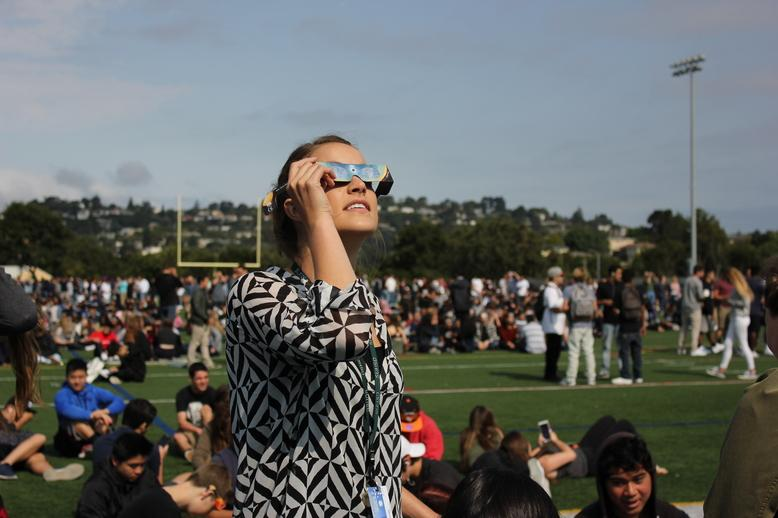 Staff+members+watch+the+solar+eclipse+with+their+students+on+the+football+field.