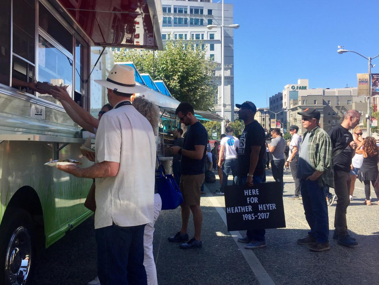 Peaceful protesters stand in line to buy food from a food truck at the rally. One man holds a