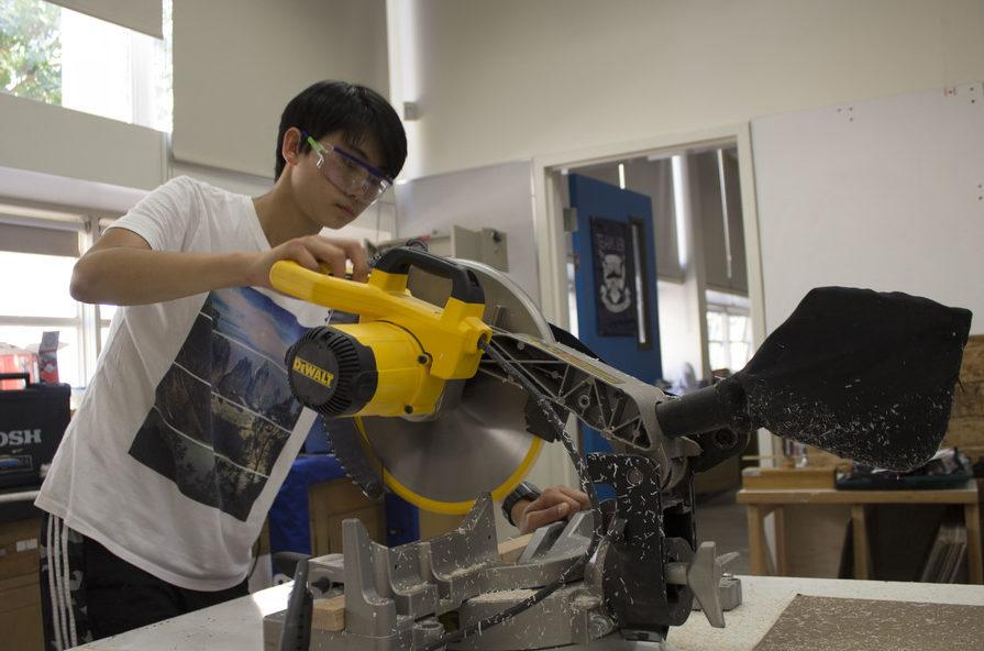 Freshman Andrew Shao uses a large cutting tool in the shop.