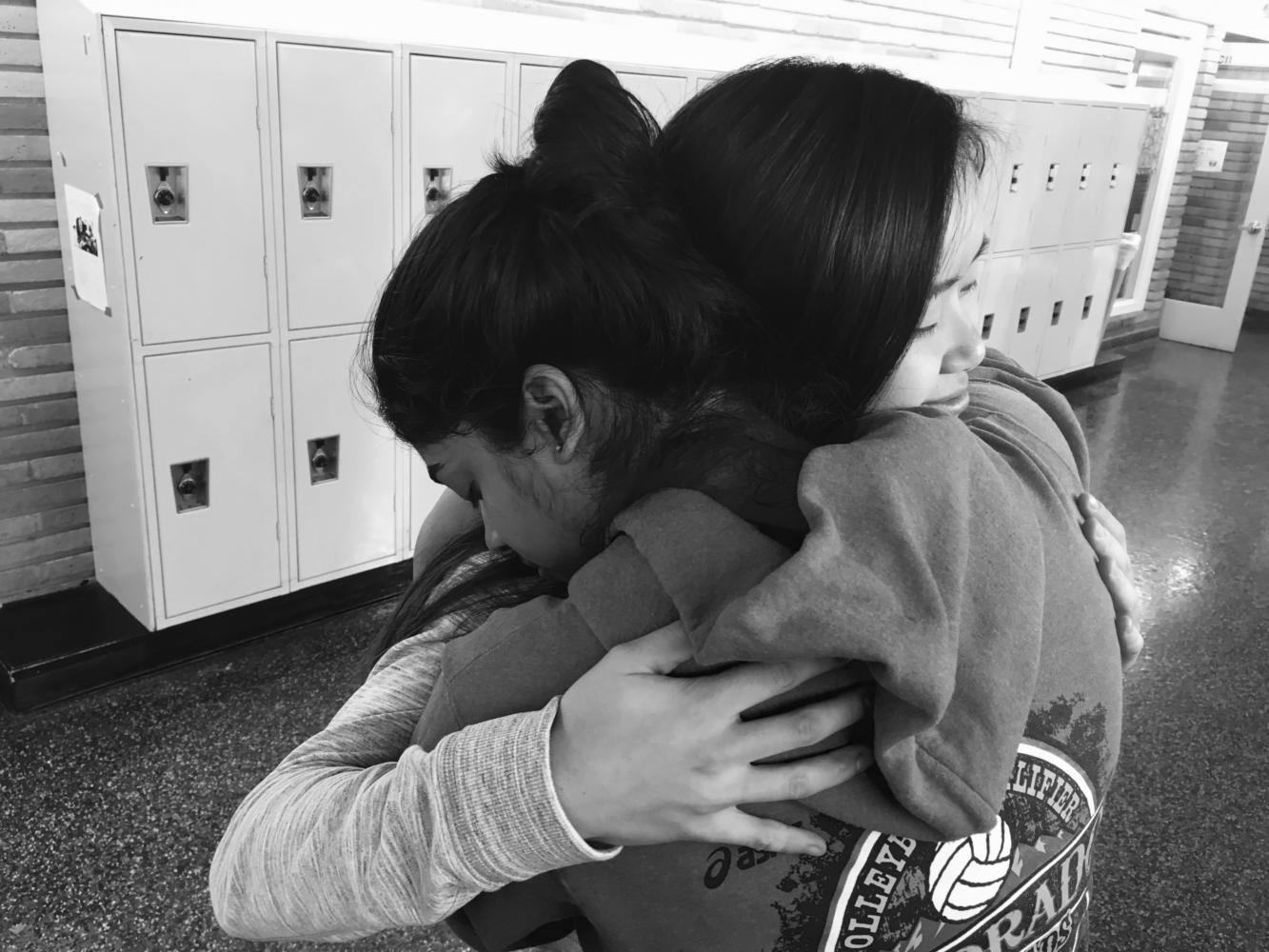 Friends share a hug in the hallway in the midst of school stress.