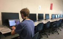 One of the club members stays in the classroom after lunch to finish their current computer science exercise.
