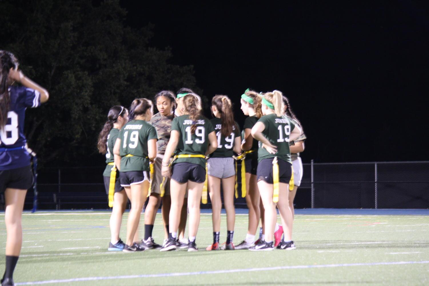 The junior team gathers for a huddle during the Powderpuff game this year against the seniors.