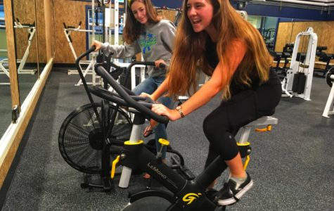 Freshmen Nyah Dompier-Norrbom and Mia Messina test out the new spin bikes.