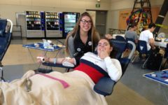 Lizzy Hall, a junior, gives blood at the Blood Drive.