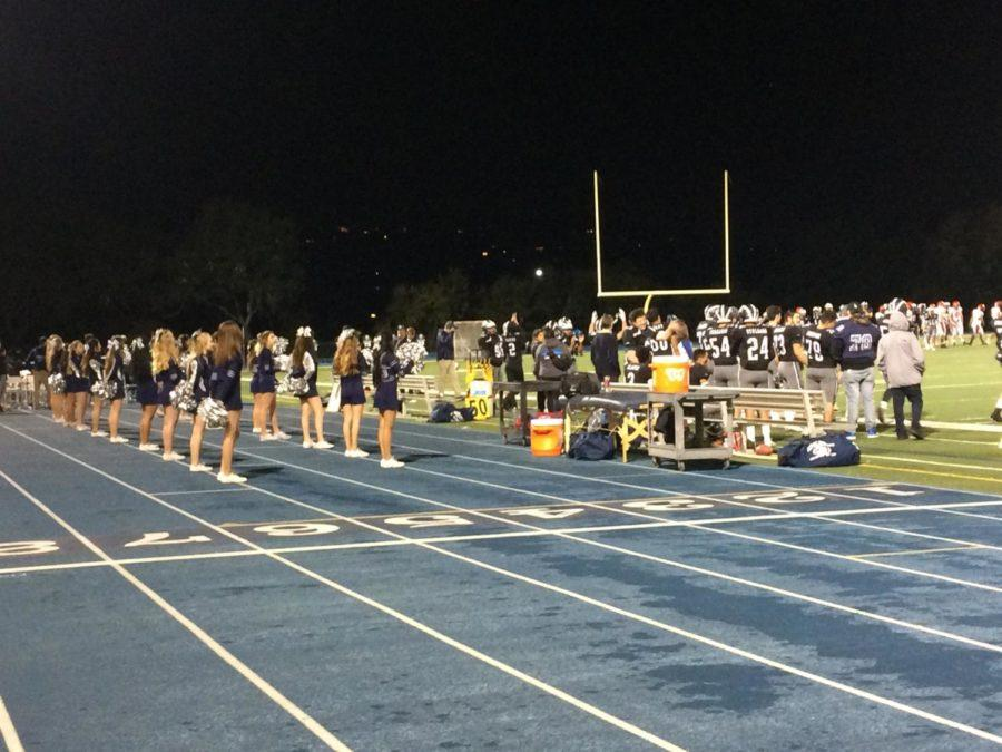 The Carlmont cheer team cheers for the varsity football team playing against Mills.