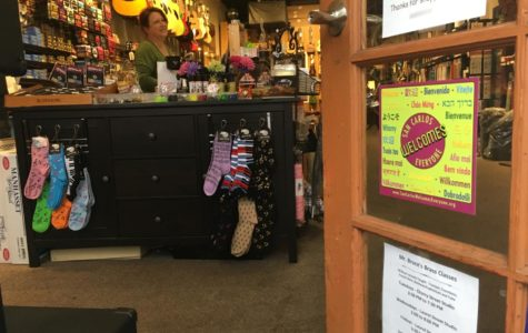 Susan Kimmel, owner of Clocktower Music, puts up a window cling sign welcoming all customers  to her store.