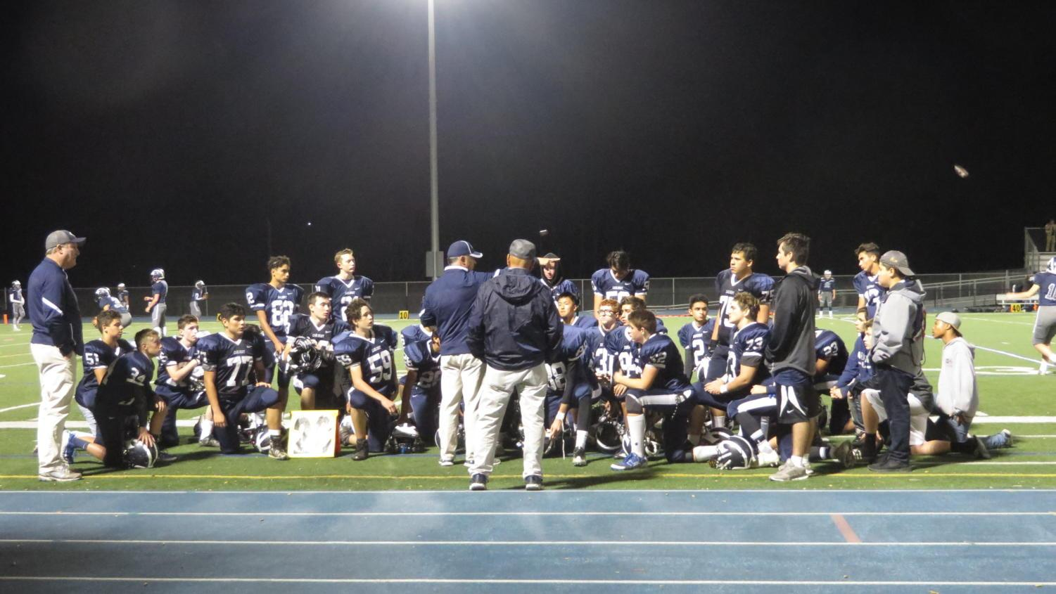 The JV team gathers around Head Coach Bruce Douglas after the game.