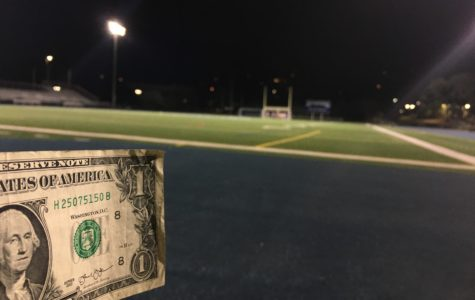 A dollar bill displayed in front of the Carlmont football field.