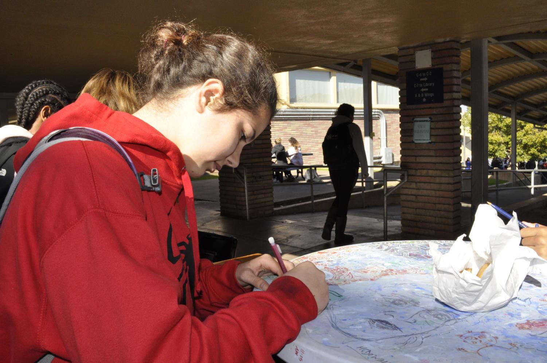 Ava Brückner-Kockel, a sophomore, writes a kind note on a holiday gram for her friend.