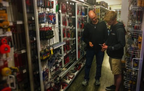 John Griesbach, a sophomore, helps a customer at ACE Hardware, the store he works at.