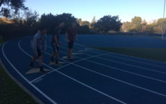 Three cross country runners are shown preparing to start their daily after-school run.