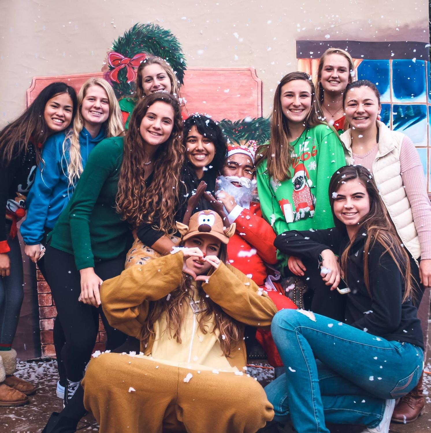 Students posed with Santa in their holiday sweaters at last year's holiday event.