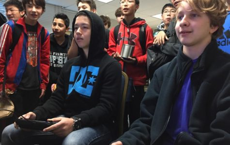 Students watch as two competitors face off in a Super Smash Bros. battle.