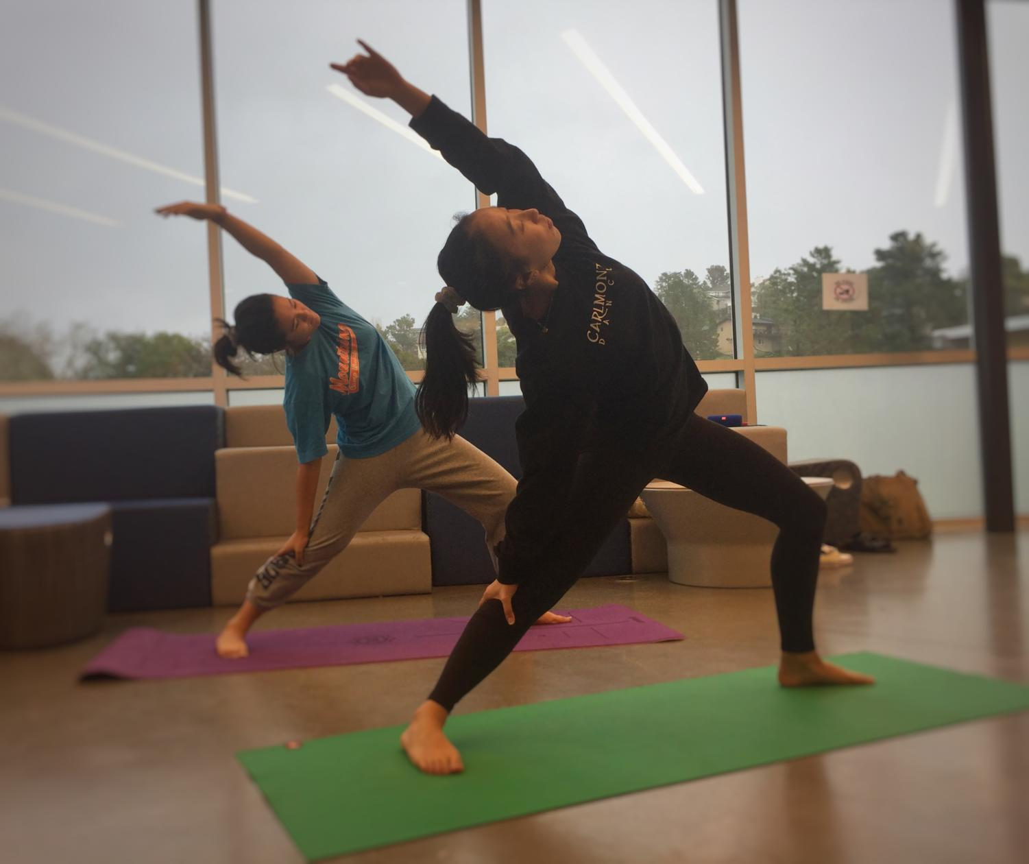 Sophomores Kenna Kwok and Sadie Somers stretch during one of Yoga Club's after-school yoga sessions.