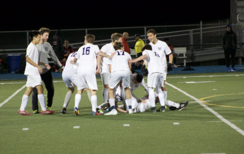The Carlmont team celebrates on the field after a goal.