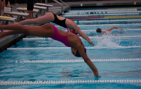 Two girls trying out for varsity dive into the pool to start their warm-up laps.