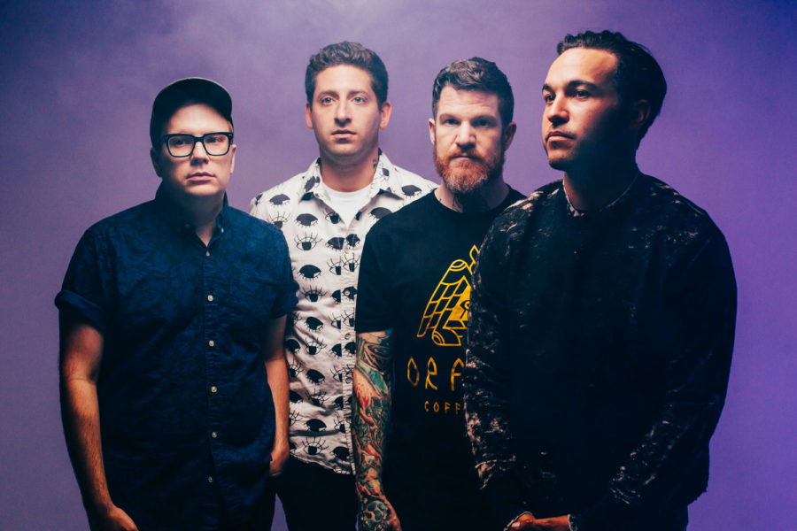 Members+of+Fall+Out+Boy+%28Patrick+Stump%2C+Joe+Trohman%2C+Andy+Hurley%2C+Pete+Wentz%29+promote+their+new+album%2C+%22M+A+N+I+A%2C%22+with+the+album+cover%27s+electronic+purple+background.