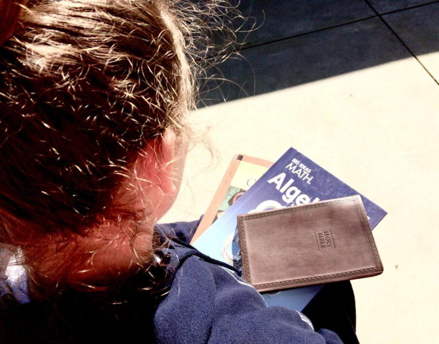 A student holds her textbooks along with her Bible as she prepares for school.