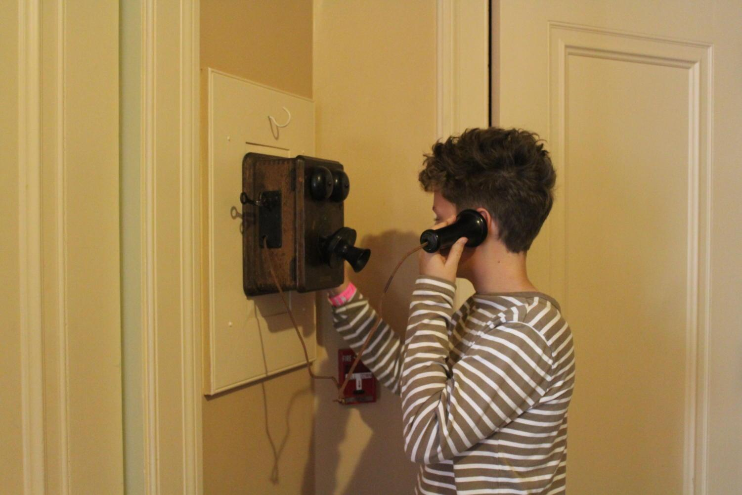 Visitor Charlie Baker uses the telephone located at the back of the Filoli house.