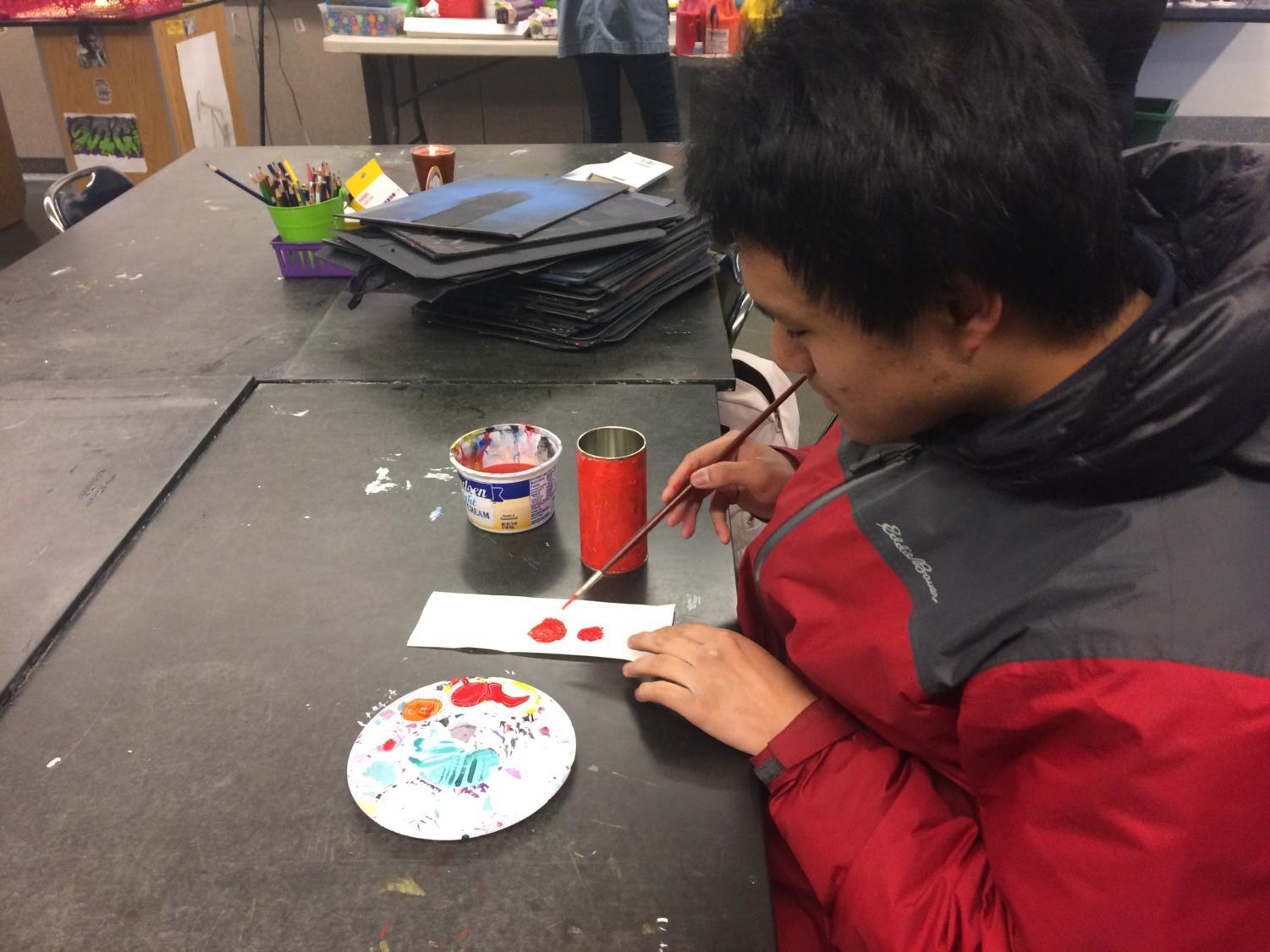 Jonathan+Yip%2C+a+senior%2C+puts+the+finishing+touches+on+his+very+own+hand+made+candle.