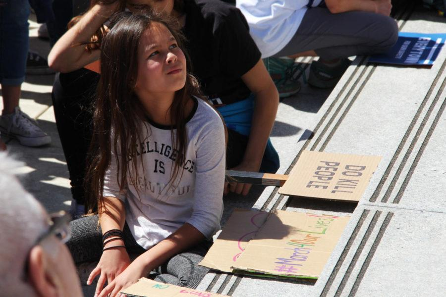 Vandenberg sits on the staircase in front of Redwood City Courthouse  and listens to student speeches.