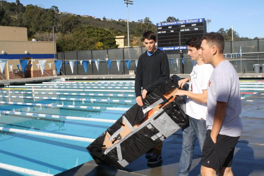 Team+members+Theo+Kelly%2C+Luke+Campbell%2C+and+Zach+Greene+get+ready+to+race+their+boat.+