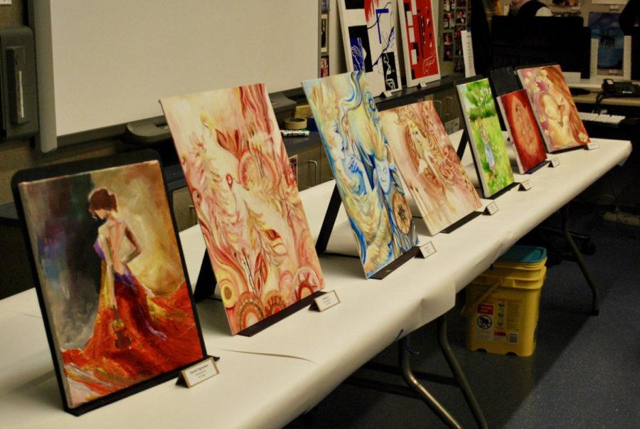 Oil paintings from the Studio Art class are displayed on tables along the front of F22 during Open House.