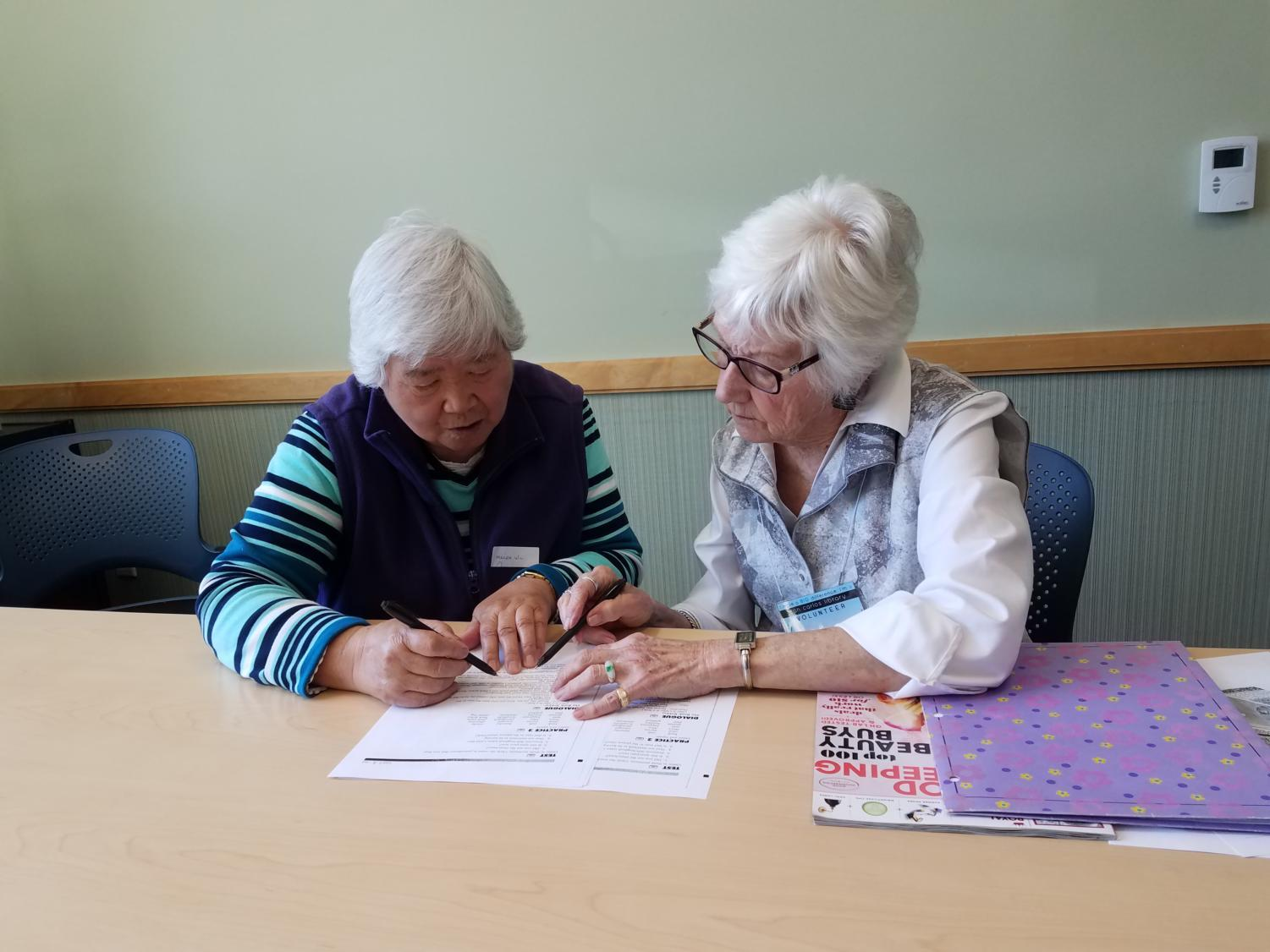 A volunteer works with a club participant on phrases associated with grocery shopping.
