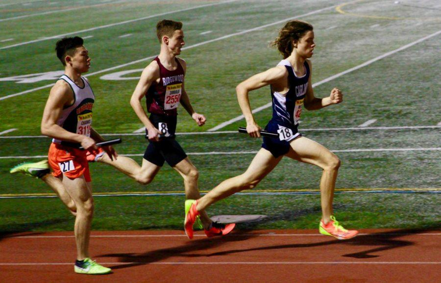 Caleb Metzler sprints past the rival schools during his third leg of the DMR.