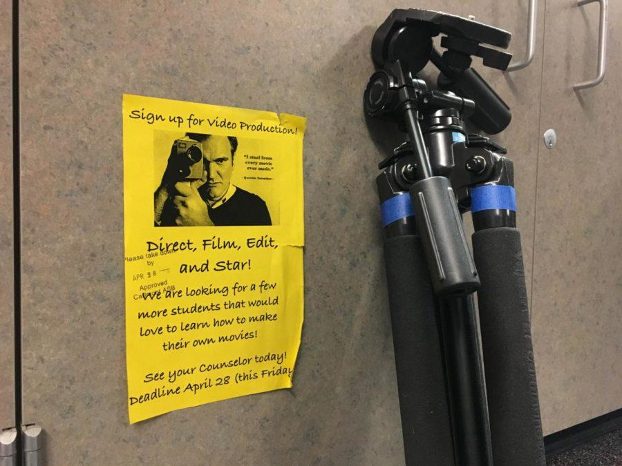 Video production flyer rests next to a tri-pod, a common stand for filming with a camera. This can be found in room F10 at Carlmont High School.