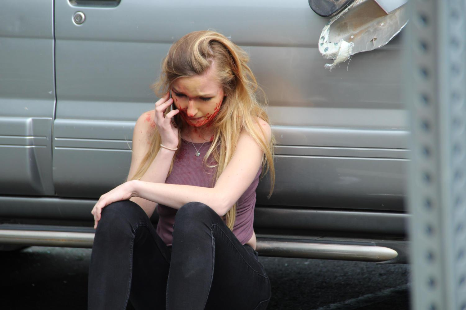 Jessica Cramer, a senior, calls 911 in a panic during the drunk-driving car crash simulation on April 15.